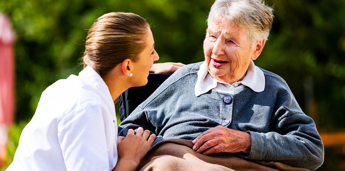 senior woman and caregiver laughing