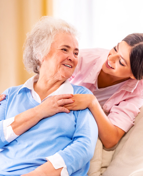 caregiver hugging elderly woman