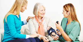 senior woman talking to her daughter and her caregiver