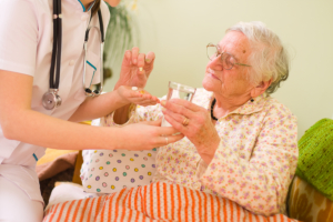 caregiver with old lady taking her medicine