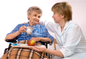 Caregiver giving food to the old lady