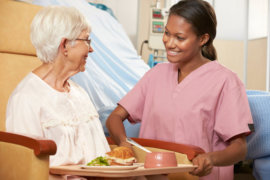 nurse serving a meal to a senior female patient who's sitting in a chair smiling